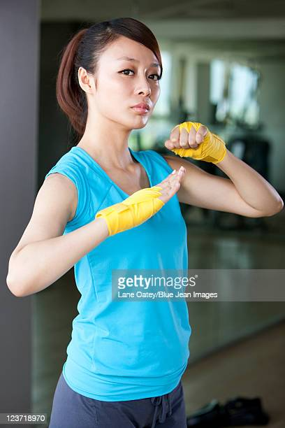 confident young woman in hand wraps - fighting stance stock pictures, royalty-free photos & images