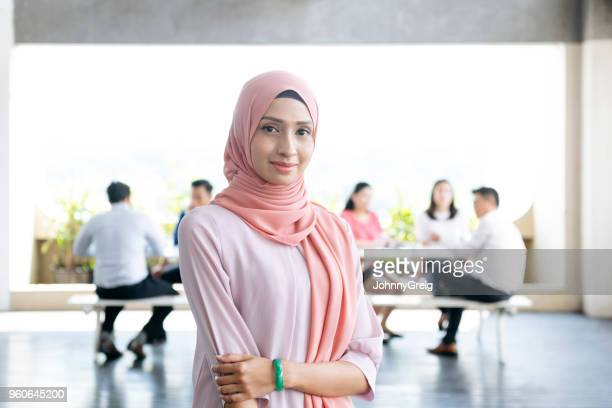 confident young woman in office smiling towards camera - malay hijab stock photos and pictures