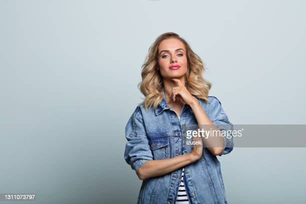 confident young woman in oversized denim jacket - 20th century stock pictures, royalty-free photos & images