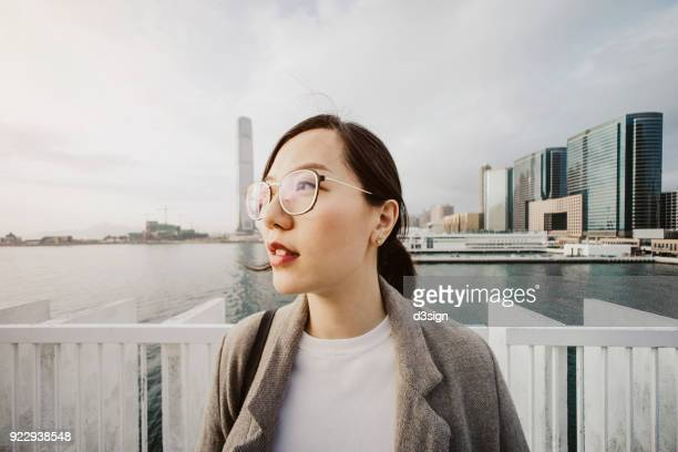 Confident young woman looks up at sky in urban pier against cityscape