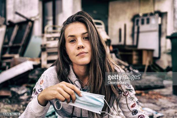 confident young woman portrait holding a face mask in her hand - homelessness stock pictures, royalty-free photos & images