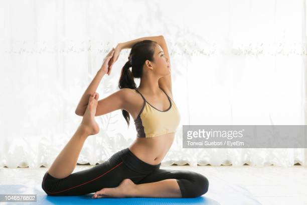 confident young woman practicing yoga against curtain at home - torwai stock pictures, royalty-free photos & images
