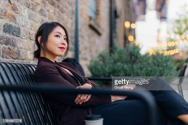 confident young woman sitting at a sidewalk cafe - chance stock pictures, royalty-free photos & images