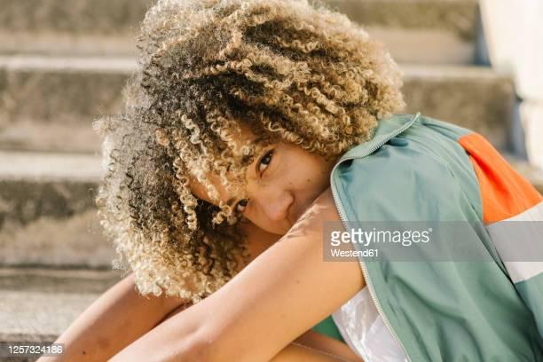 confident young woman sitting on steps during sunny day - kroeshaar stockfoto's en -beelden
