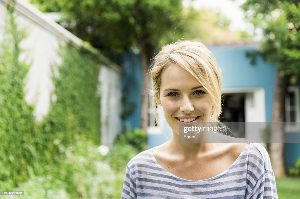 Confident young woman smiling in backyard : Stock Photo