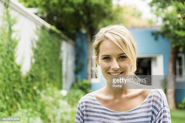 Confident young woman smiling in backyard