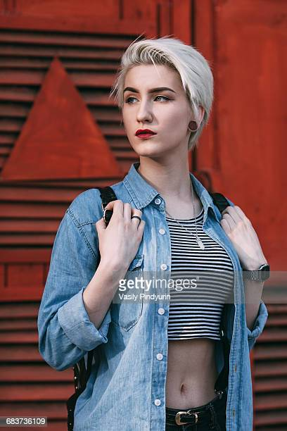 Confident young woman standing against red brick wall