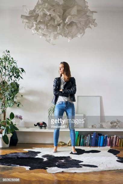 confident young woman standing on fur in a room - giacca di pelle foto e immagini stock