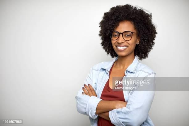 confident young woman standing with arms crossed - braços cruzados - fotografias e filmes do acervo