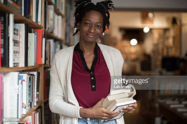 Confident young woman standing with books