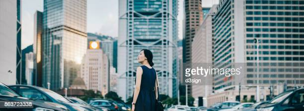 confident young woman surrounded by highrise financial buildings in central business district in city - central stock pictures, royalty-free photos & images