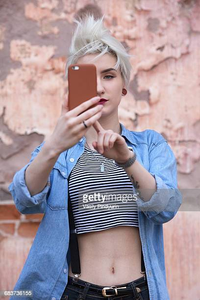 Confident young woman taking selfie through smart phone while standing against wall