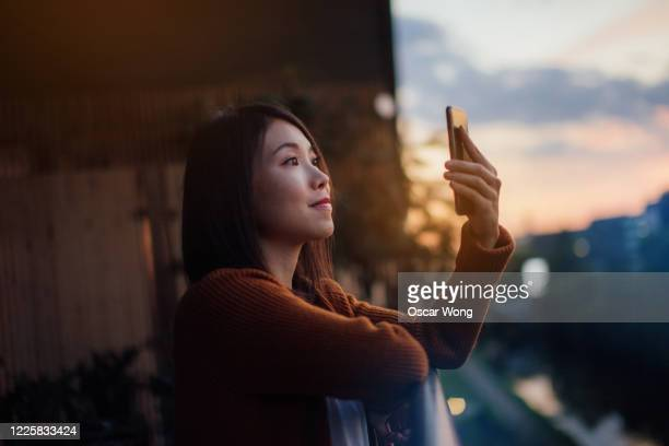 confident young woman using smart phone at the balcony - japanese ethnicity stock pictures, royalty-free photos & images