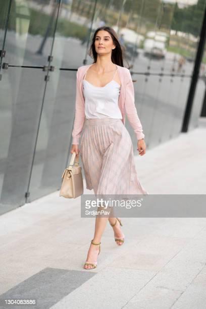jeune femme confiant marchant - jupe photos et images de collection