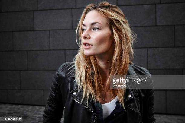 confident young woman wearing biker jacket looking away - biker jacket stock pictures, royalty-free photos & images