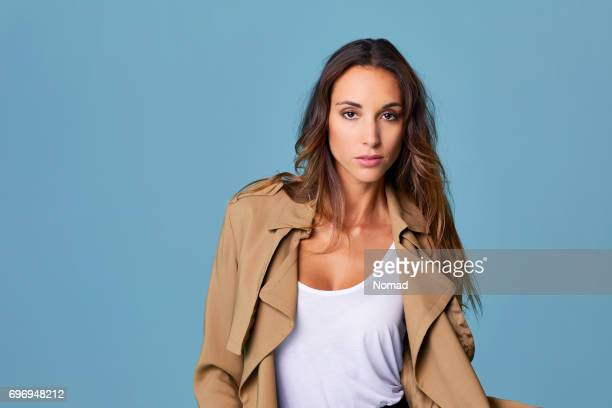 confident young woman wearing brown trench coat - brown coat stock pictures, royalty-free photos & images