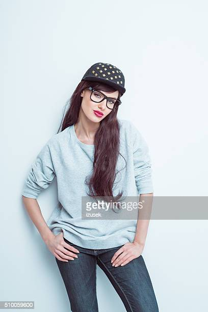 Confident young woman wearing nerd glasses and baseball cap