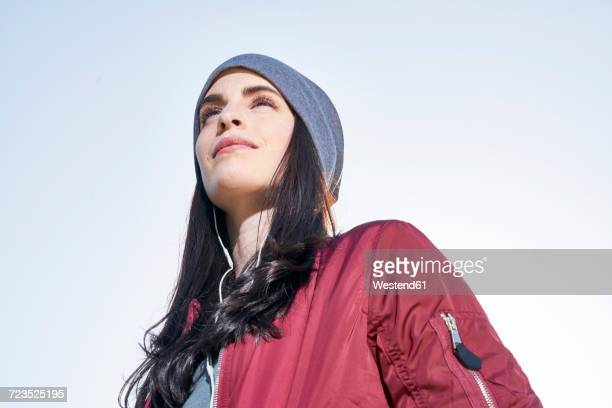 Confident young woman with earbuds outdoors