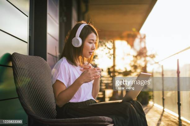 confident young woman with headphones having a conference call on laptop at the balcony - the internet stock pictures, royalty-free photos & images
