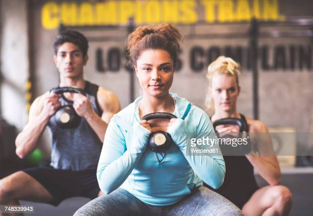 Confident young woman with training partners lifting kettlebell in gym