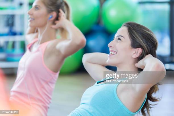 Confident young women do sit ups at the gym