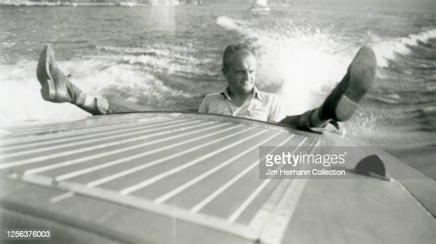 A confidentlooking man sits on the back of speedboat with legs spread wide open making it look as though he backside is dragging along the water...
