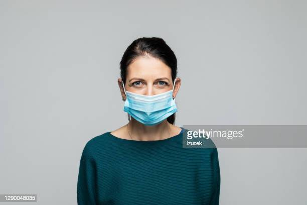 vertrouwde vrouw die beschermend gezichtsmasker draagt - izusek stockfoto's en -beelden
