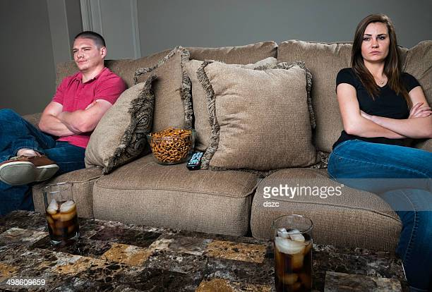 conflicted couple watching TV; unhappy, angry, and ignoring each other