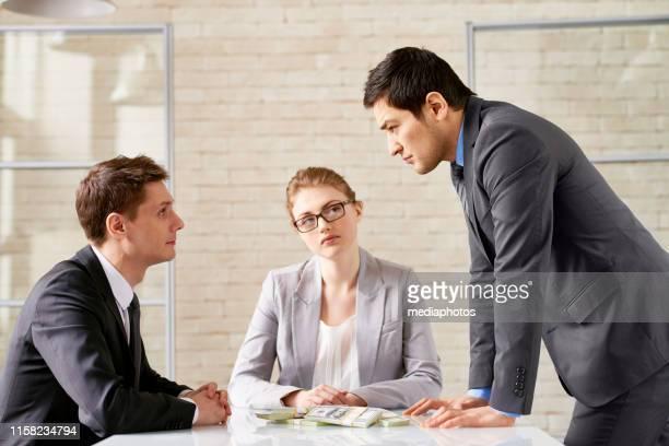 empresario conflictivo con banquero en la mesa - conflicto fotografías e imágenes de stock