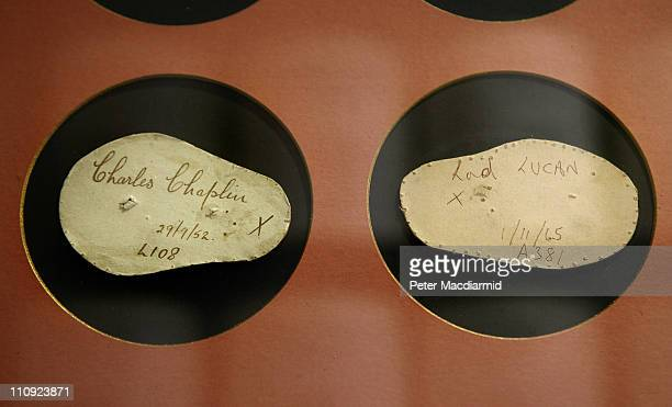 Conforms which are a copy of the shape of a persons head from Charlie Chaplin and Lord Lucan are displayed behind glass at Lock Co Hatters on March...