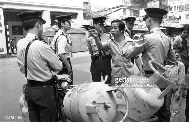 ConfrontationPolicemen stop a delivery man for carrying an excessive load on his bicycle namely five liquefied petroleum gas cylinders in Wan Chai...