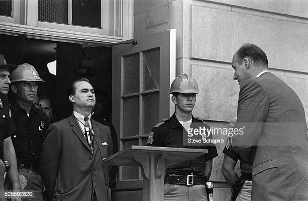 Confronted by US Justice Department officials Alabama Governor George C Wallace keeps his promise to Alabama voters 'to stand in the schoolhouse...