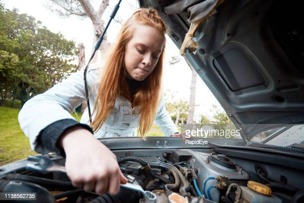 confused and irritated young redhead attempts to fix her car - ineptitude stock pictures, royalty-free photos & images
