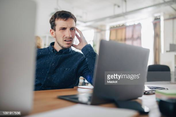 confused businessman looking at laptop while sitting at desk in office - confusão - fotografias e filmes do acervo