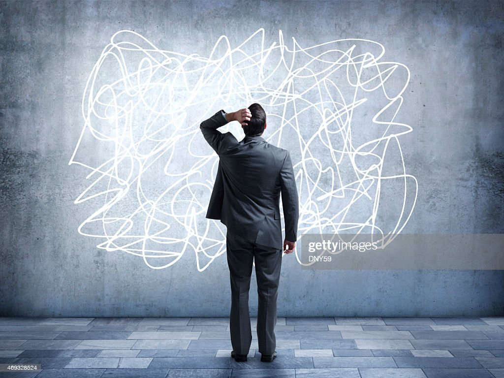 Confused businessman staring at scribble on wall : Stock Photo