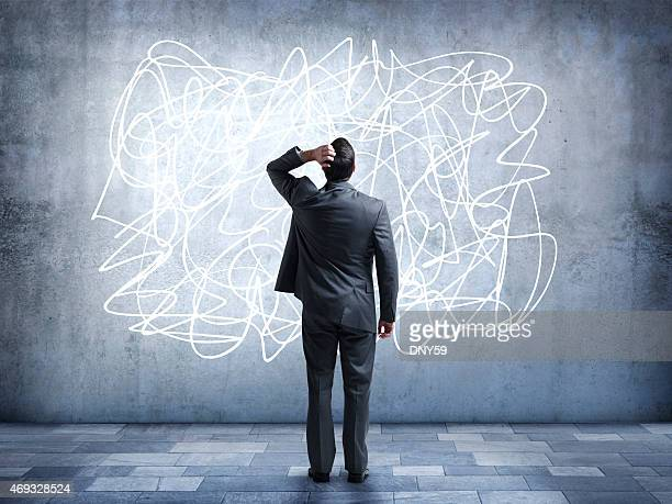 Confused businessman staring at scribble on wall