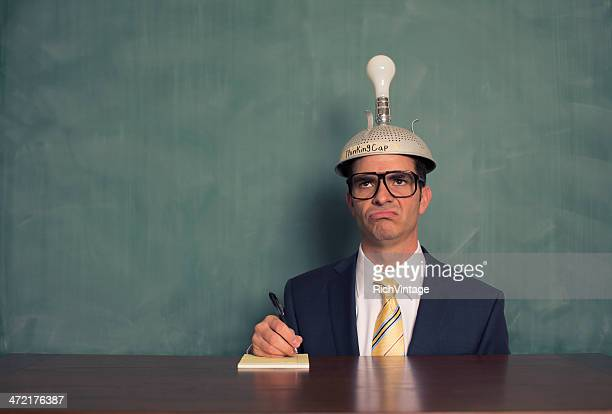 Confused Businessman Wearing Unlit Thinking Cap at Desk