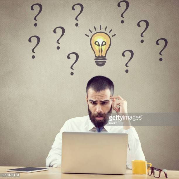Confused businessman working on laptop