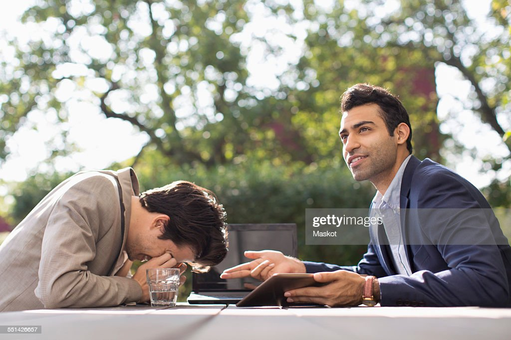 Confused businessmen being stumbled at outdoor cafe : Stock Photo