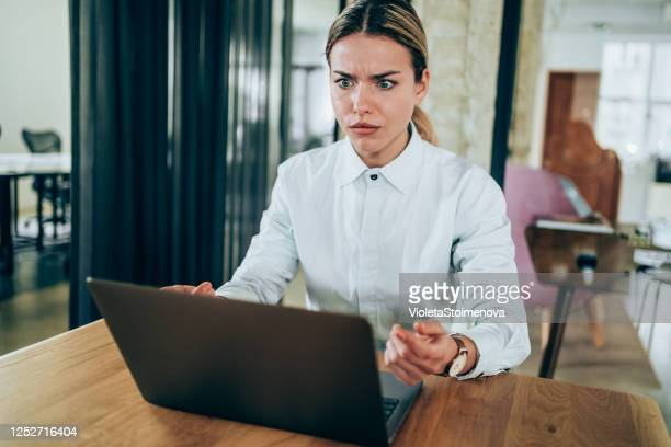 confused businesswoman looking at laptop. - mistake stock pictures, royalty-free photos & images