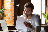 Confused frustrated man reading letter in cafe, receiving bad news