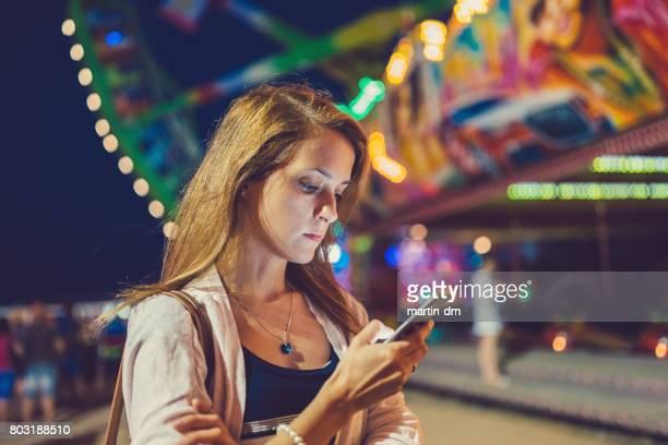 Chica confundida en el parque de atracciones con smartphone