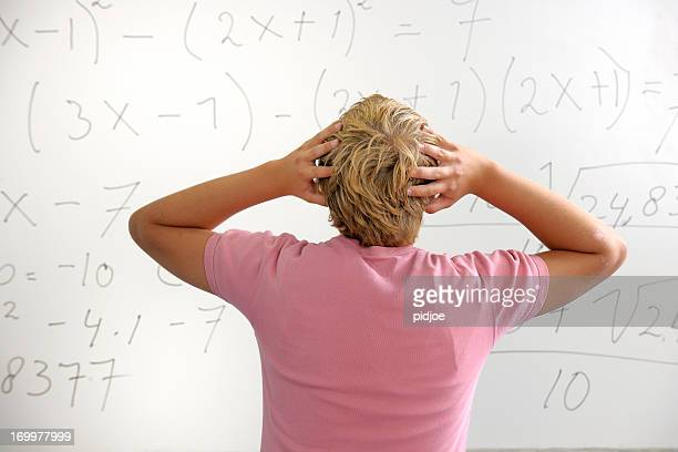 confused high school student in front of whiteboard