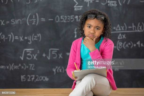 Confused little girl works on math homework