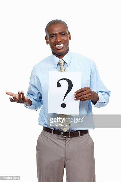 Confused looking man holding a question mark sign
