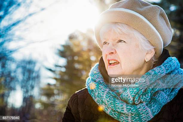 Confused lost senior woman walking outdoors in winter clothing