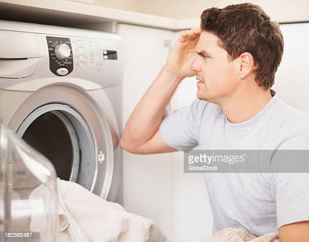 Confused man adjusting the controls of washing machine