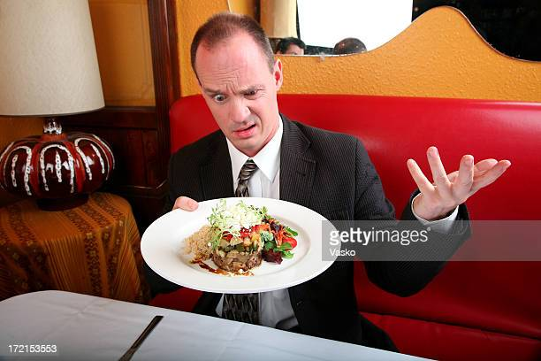 Confused man holding a plate of food in a restaurant