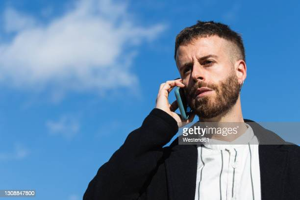 confused man talking on smart phone against sky - 35 39 years stock pictures, royalty-free photos & images