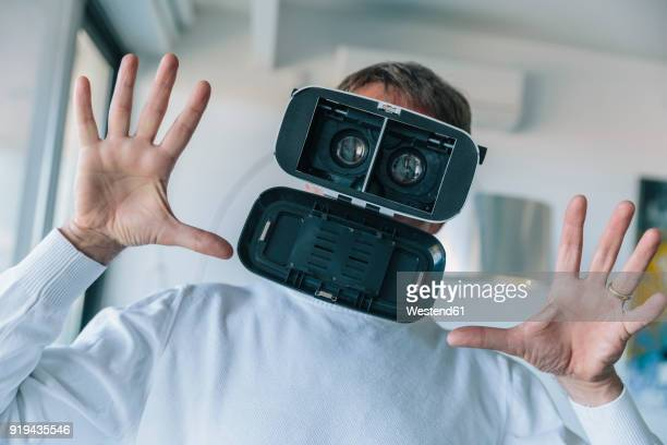 Confused man wearing VR glasses making a crazy face